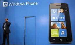 Мужчина говорит по мобильному телефону, стоя около рекламы ОС Windows Phone на мобильном конгрессе в Барселоне, 27 февраля 2012 года. Microsoft Corp рассматривает возможность выпуска собственного смартфона для того, чтобы подстегнуть продажи мобильной операционной системы Windows, сообщает аналитик Уолл-стрит, многие годы следящий за делами компании. REUTERS/Albert Gea