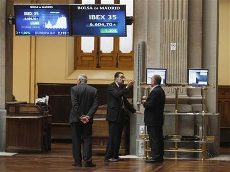 Traders speak to one another below to electronic boards at the Madrid stock exchange June 19, 2012. REUTERS/Andrea Comas