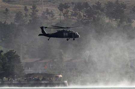 Smoke rises from a hotel as a NATO helicopter flies over the site of attack outside of Kabul June 22, 2012. REUTERS/Omar Sobhani