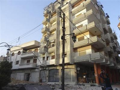 A man takes photos of damaged buildings at Al Khalidieh near Homs June 17, 2012. REUTERS/Waleed Fares/Handout