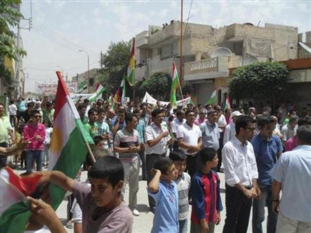 Demonstrators hold Kurdish and Syrian opposition flags during a protest against Syria's President Bashar al-Assad at Kalbouni near Aleppo June 22, 2012. REUTERS/Shaam News Network/Handout