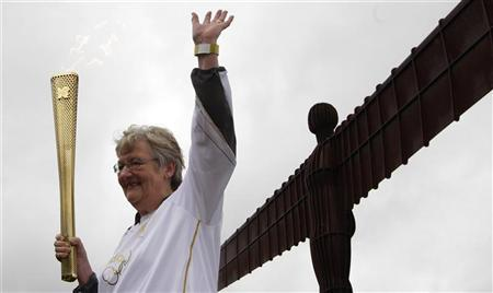 Torch bearer Iris Hutchinson waves while holding a London 2012 Olympic Games torch at the Angel of the North sculpture near Gateshead, north east England June 16, 2012. REUTERS/David Moir