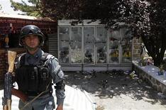An Afghan policeman keeps watch at the site of an attack at a hotel on the outskirts of Kabul June 22, 2012. REUTERS/Mohammad Ismail