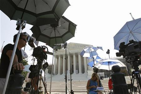 TV camera crew protect themselves from the sun during a stakeout at the U.S. Supreme Court in Washington June 21, 2012. REUTERS/Jose Luis Magana