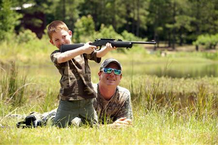 Jeremy Chavez helps his son Ryan, 6, with target practice before a wild hog hunt at Great Southern Outdoors Wildlife Plantation in Union Springs, Alabama, Saturday June 16, 2012. REUTERS/Michael Spooneybarger