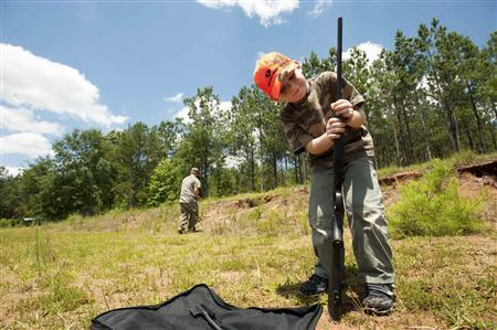 Ryan Chavez, 6, hunting with his dad Jeremy Chavez, prepares his gun for target practice before a wild hog hunt at Great Southern Outdoors Wildlife Plantation in Union Springs, Alabama, June 16, 2012. REUTERS/Michael Spooneybarger