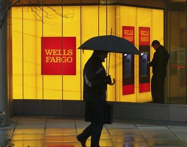 A man walks past a Wells Fargo Bank branch on a rainy morning in Washington in this January 17, 2012 file photo. REUTERS/Gary Cameron/Files