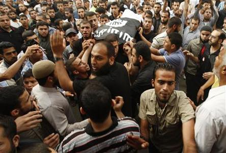 Palestinians carry the body of militant Basil Ahmed during his funeral in al-Bureij refugee camp in the central Gaza Strip June 22, 2012. REUTERS/ Ibraheem Abu Mustafa