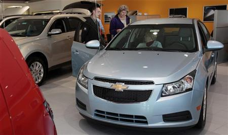 Suburban Chevrolet dealership sales person Scott Northway shows two potential customers a Chevrolet Cruze on display at the dealership in Ann Arbor, Michigan, October 22, 2011. REUTERS/Rebecca Cook