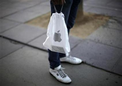 A man carries a bag out of an Apple store in Santa Monica, California March 13, 2012. REUTERS/Lucy Nicholson/Files