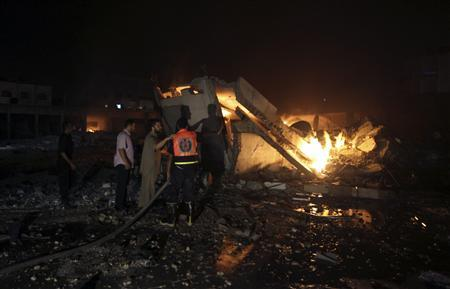 Palestinians try to douse a fire after Israeli air raids hit a Hamas security site in Gaza City June 23, 2012. REUTERS/Mohammed Salem