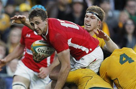 Wales' Ashley Beck (L) is tackled by Australian players during their international rugby test match in Sydney June 23, 2012. REUTERS/Daniel Munoz