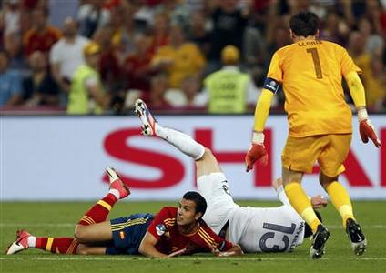 Spain's Pedro Rodriguez (L) lies on the ground after he was fouled during their Euro 2012 quarter-final soccer match against France at the Donbass Arena in Donetsk, June 23, 2012. REUTERS/Charles Platiau