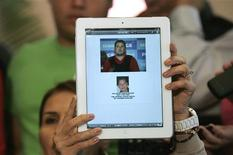 Lawyer Veronica Guerrero holds up a tablet to show a combination of photos of her client Felix Beltran, detained by Mexican marines on Thursday, during a news conference in Guadalajara June 22, 2012. REUTERS/Alejandro Acosta
