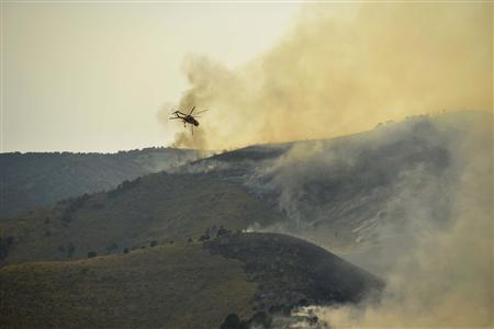 A helicopter carries water from Utah Lake to fight the Dump fire near Saratoga Springs, Utah, June 22, 2012. REUTERS/Jeff McGrath