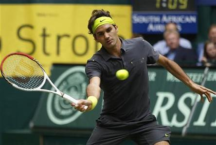 Roger Federer of Switzerland returns a ball to Tommy Haas of Germany during their men's singles final at the Halle Open ATP tennis tournament in Halle June 17, 2012. REUTERS/Ina Fassbender (GERMANY - Tags: SPORT TENNIS)