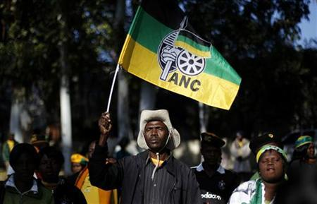 An African National Congress (ANC) supporter holds the party's flag during a march to the Goodman Gallery in Johannesburg May 29, 2012, where a portrait exposing South African President Jacob Zuma's genitals were first displayed. REUTERS/Siphiwe Sibeko