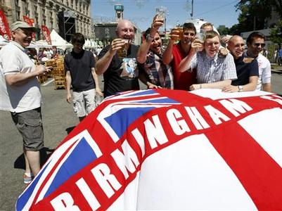 English soccer fans pose for pictures in the fan zone in Kiev, June 24, 2012. England will play its quarter-final of the Euro 2012 soccer championships against Italy in Kiev on Sunday. REUTERS/Anatolii Stepanov