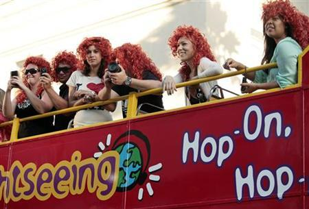 Fans wear red wigs as they watch arrivals from a double-decker bus at the premiere of Disney Pixar's ''Brave'' in Hollywood, California June 18, 2012. REUTERS/Jason Redmond
