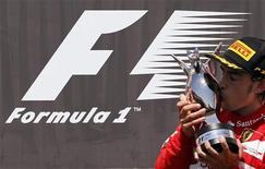 Piloto da Fórmula 1 Fernando Alonso, da Espanha, beija seu troféu no pódio após vencer o Grande Prêmio da Europa de F1 no circuito de rua de Valência. 24/06/2012 REUTERS/Albert Gea