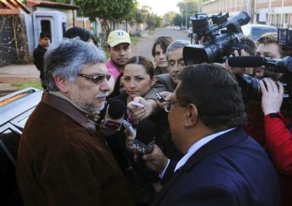 Ousted Paraguayan President Fernando Lugo (L) talks to journalists outside his home in Lambare, on the outskirts of Asuncion, June 23, 2012. REUTERS/Stringer