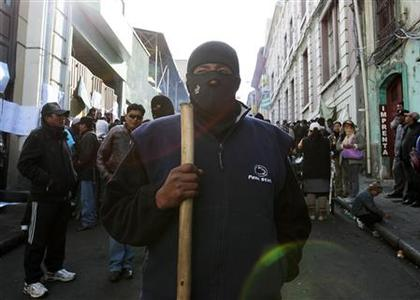 A police officer in civilian clothing takes part in a riot in La Paz June 24, 2012. Some members of the police and their wives occupied police barracks and marched in their fourth day of protests against low wages according to local media. REUTERS/David Mercado