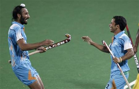 India's Bharat celebrates with his teammate Sardar Singh (L) after scoring a goal against Malaysia during their hockey group match at the Commonwealth Games in New Delhi October 5, 2010. REUTERS/Adnan Abidi