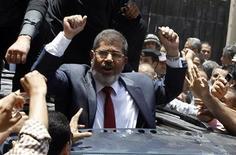 """Мохамед Мурси приветствует своих сторонников после выхода с избирательного участка 16 июня 2012 года. Избранный в воскресенье президентом Египта Мохамед Мурси из исламистского движения """"Братья-мусульмане"""" приступил к созданию гражданского правительства, что может исцелить исторические травмы, вызванные притеснением, и убедить недоверчивую армейскую верхушку ослабить влияние на власть. REUTERS/Ahmed Jadallah"""