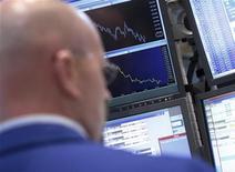 Трейдер следит за ходом торгов на бирже в Нью-Йорке, 21 июня 2012 года. Уолл-стрит миновала несколько крупных препятствий на прошлой неделе - выборы в Греции и сокращение ФРС прогнозов роста экономики США - но драма еще не завершилась. REUTERS/Brendan McDermid