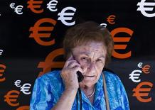 A woman speaks on her mobile phone as she stands next to euro signs in Madrid June 21, 2012. REUTERS/Susana Vera
