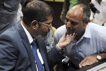 Muslim Brotherhood's president-elect Mohamed Morsy (L) speaks to a television director at the Egyptian Television headquarters control room before his first televised address to the nation in Cairo June 24, 2012. Morsy's victory in Egypt's presidential election takes the Muslim Brotherhood's long power struggle with the military into a new round that will be fought inside the institutions of state themselves and may force new compromises on the Islamists. Picture taken June 24, 2012. REUTERS/Stringer