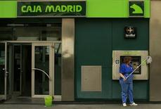 A cleaner cleans the facade of a Bankia-Caja Madrid bank branch in the Andalusian capital of Seville June 25, 2012. Spain formally requested European aid for its banks on Monday but did not specify how much money it will seek to recapitalize the indebted lenders. REUTERS/Marcelo del Pozo