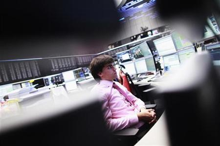 A trader looks at screens at the Frankfurt stock exchange June 18, 2012. REUTERS/Alex Domanski