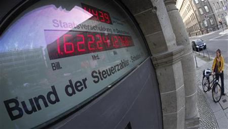 A woman pushes a bicycle past a building with the so-called Schuldenuhr (debt clock) which indicates the current German national debt per second, in Berlin October 7, 2009. The European Union's executive launched disciplinary action on Wednesday against Germany, Italy and seven other countries for letting their budget deficits rise above the bloc's permitted ceiling. REUTERSFabrizio Bensch (GERMANY BUSINESS POLITICS IMAGES OF THE DAY)