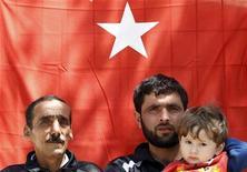 Сирийские беженцы стоят на фоне национального флага Турции в лагере беженцев Яайладаги у границы с Сирией 17 апреля 2012 гда. Сирийский генерал и 38 солдат бежали в Турцию в ночь на понедельник, через два дня после того, как Сирия сбила турецкий военный самолет, сообщило государственное телевидение Дамаска. REUTERS/Umit Bektas