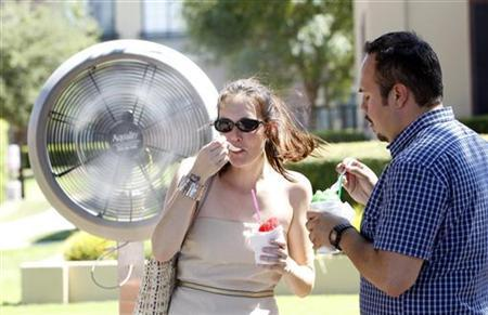 Alana Coates (L) and Ricardo Briones, both of San Antonio, stand in front of a misting fan and enjoy an icy treat while while enduring the extreme temperatures on a visit to the Stockyards in Fort Worth, Texas August 5, 2011. REUTERS/Mike Stone