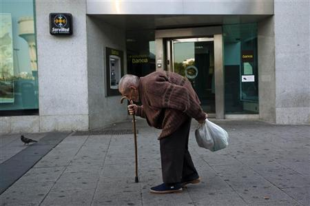 An elderly man walks past a branch of Spain's lender bank Bankia in Madrid June 25, 2012. REUTERS/Susana Vera
