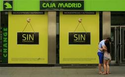 A couple embraces in front of the Bankia-Caja Madrid bank branch in the Andalusian capital of Seville June 25, 2012. Spain formally requested European aid for its banks on Monday but did not specify how much money it will seek to recapitalize the indebted lenders. REUTERS/Marcelo del Pozo