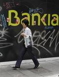 Женщина проходит мимо логотипа банка Bankia в Мадриде, 8 июня 2012 года. Агентство Moody's Investors Service в понедельник сократило долгосрочные долговые и депозитные рейтинги 28 испанских банков после того, как ранее в июне снизило суверенный рейтинг страны на три ступени. REUTERS/Andrea Comas