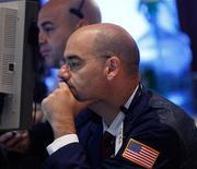 Трейдер следит за ходом торгов на бирже в Нью-Йорке, 25 июня 2012 года. Американские акции резко снизились в понедельник, так как инвесторы не видят причин для оптимизма перед саммитом Евросоюза на этой неделе. REUTERS/Brendan McDermid