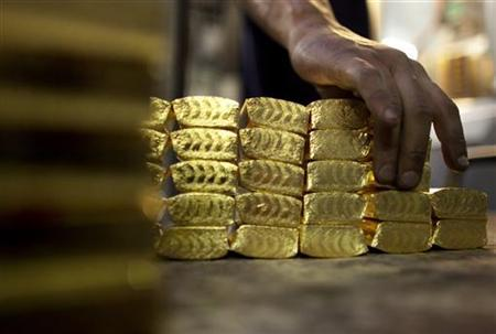 A worker grabs pre-cast bars of gold at a plant of refiner and bar manufacturer Argor-Heraeus SA in the southern Swiss town of Mendrisio, March 1, 2012. REUTERS/Pascal Lauener