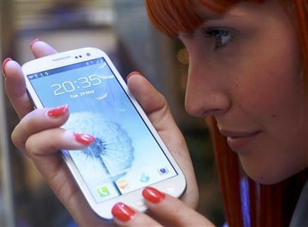 A shop assistant poses with the new Samsung Galaxy S III after it's launch at the Westfield shopping centre in west London, May 29, 2012. REUTERS/Olivia Harris