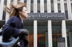 Женщина проходит мимо здания офиса NewsCorp в Нью-Йорке, 8 февраля 2012 года. Медиахолдинг Руберта Мёрдока News Corp думает о разделении себя на две компании, сообщает Wall Street Journal со ссылкой на людей, знакомых с ситуацией. REUTERS/Brendan McDermid