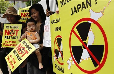 A mother and her child join a protest against the Japanese government's decision to restart two nuclear reactors, in front of the Japanese embassy in Bangkok June 15, 2012. REUTERS/Sukree Sukplang