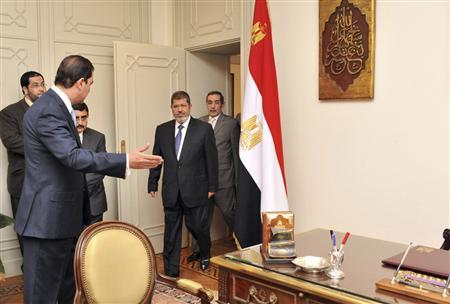 Muslim Brotherhood's President-elect Mohamed Mursi (C) arrives to his office at the Presidency, in Cairo June 25, 2012. REUTERS/Middle East News Agency (MENA)/Handout