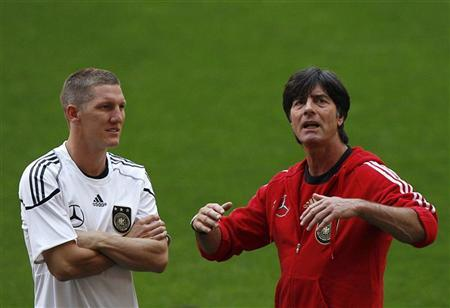 Germany's national soccer coach Joachim Loew (R) talks to his player Bastian Schweinsteiger during a training session at Turk Telekom Arena in Istanbul October 6, 2011. REUTERS/Murad Sezer