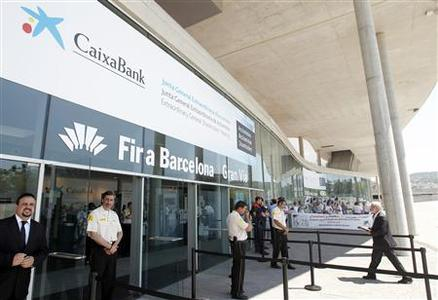 People protest at the entrance of Caixabank's extraordinary general shareholders meeting, where the approval of the decision for the merger of the bank by absorbing Banca Civica will be made, in Barcelona June 26, 2012. REUTERS/Albert Gea