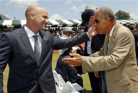 Andre Agassi (L) hugs coach Nick Bollettieri after Agassi was inducted into the International Tennis Hall of Fame in Newport, Rhode Island July 9, 2011. REUTERS/Brian Snyder