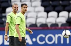 Portugal's Cristiano Ronaldo (R) and Pepe attend a training session before their Euro 2012 semi-final soccer match against Spain, at Shakhtar stadium in Donetsk June 26, 2012. REUTERS/Alessandro Bianchi