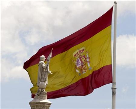A statue of Christopher Columbus with an extended hand is seen in front of a Spanish flag in central Madrid June 11, 2012. REUTERS/Paul Hanna